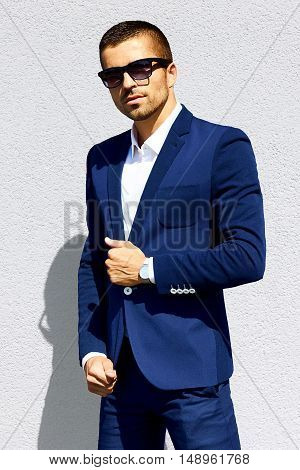 young handsome sexy man in a blue suit on a background of gray wall
