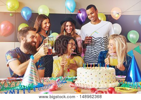 Group of Caucasian and African friends at party. Large white frosting birthday cake and decorations on top of table.