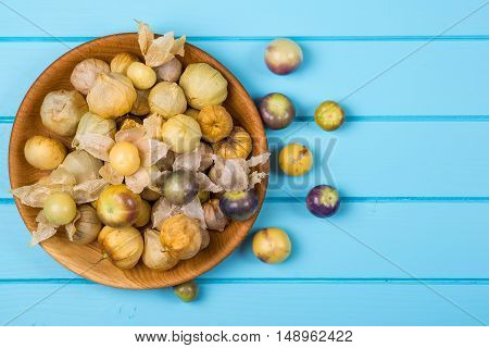 Ripe physalis in the blue wooden bowl.