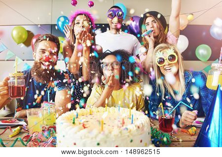 Confetti flying around group celebrating a party with large cake and drinks on table in front of them