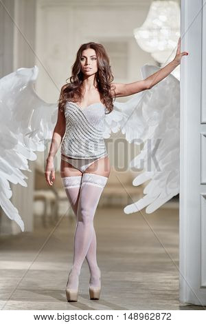 Young woman in white underwear, stockings and angel wings behind her back in room against doorway with her hand on door.