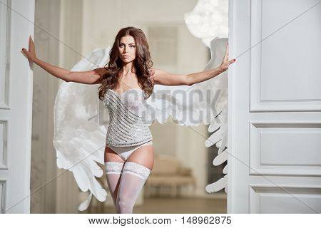 Young woman in white underwear, stockings and angel wings behind her back in room against doorway with her hands on doors.