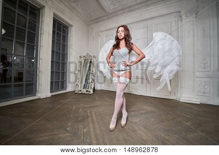 Young woman in white underwear, stockings and angel wings behind her back walks along room with her hands akimbo.