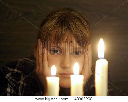 The face of a beautiful girl and three burning candles. Portrait