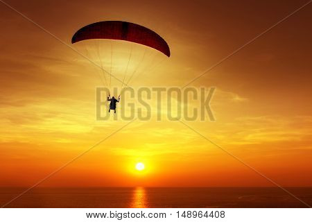 Silhouette of skydiver on background of sunset sky and sea
