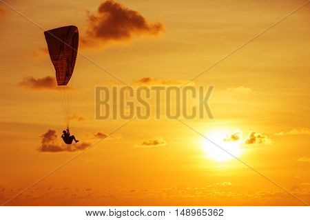 Silhouette of skydiver on background sunset and the sea