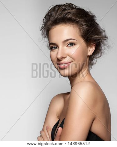 Beautiful smiling girl with clean skin natural make-up and white teeth on grey background