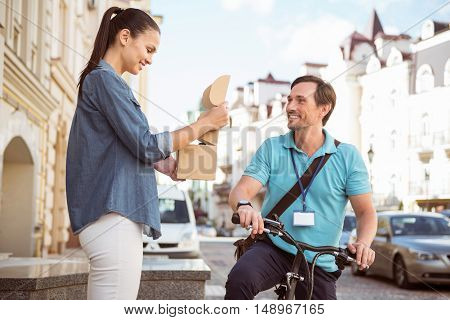 Is everything here. Joyful professional smiling courier delivering the parcel while his smiling client standing on the porch and opening the box