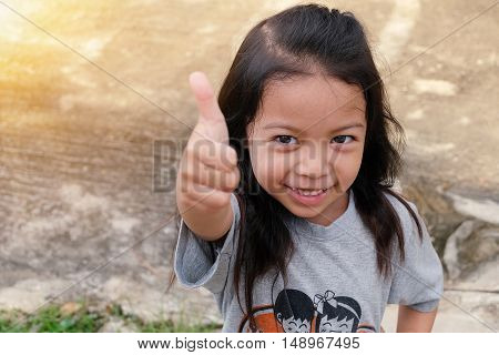 Portrait of cute little girl thump up
