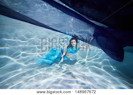 Young black-haired woman in blue dress poses underwater under dark-blue fabric with her eyes open.