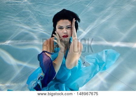 Young black-haired woman in blue dress poses underwater with her eyes open and hands around  her face.