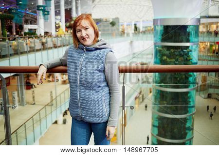 Red-haired smiling woman stands leaning at railing on upper floor of mall.