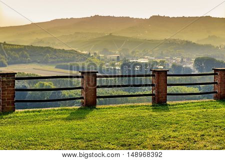 Langhe hills and fence during golden hour as seen from Grinzane Cavour Castle park in Italy