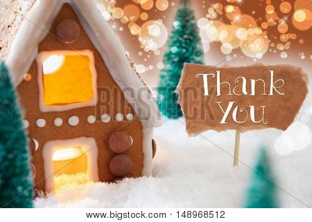Gingerbread House In Snowy Scenery As Christmas Decoration. Christmas Trees And Candlelight For Romantic Atmosphere. Bronze And Orange Background With Bokeh Effect. English Text Thank You