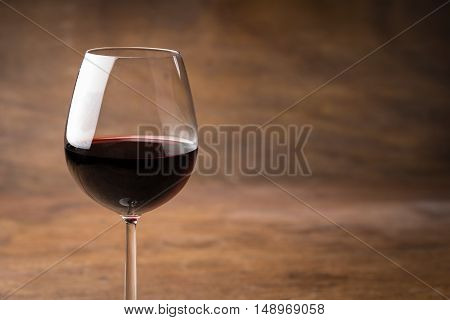 Glass of delicious mulled red wine for keeping warm in winter over an oak table background with copy space