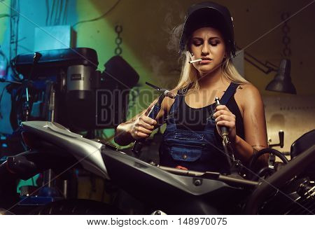 Woman mechanic working in a motorcycle workshop