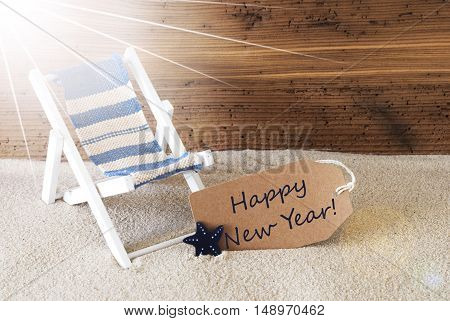 Sunny Summer Label With Sand And Aged Wooden Background. English Text Happy New Year. Deck Chair For Holiday Or Vacation Feeling.
