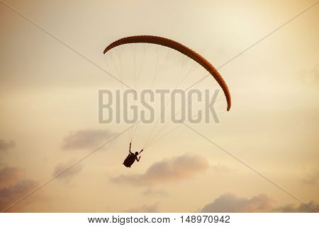 Paraglider flies on background of the sea and sunset