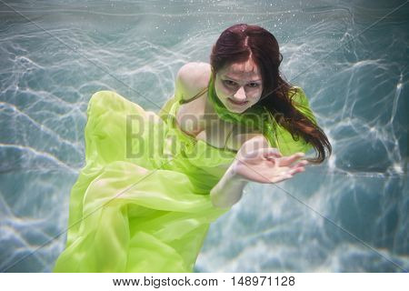 Smiling young woman in yellow-green dress poses in swimming pool underwater.