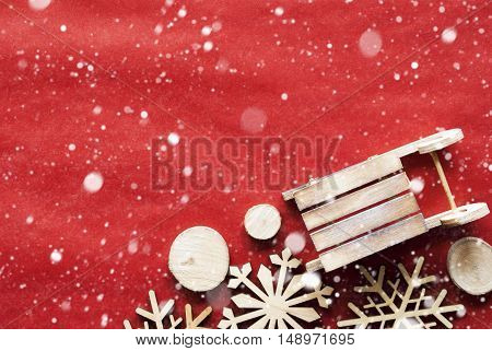 Christmas Decoration Like Wooden Sleigh And Snowflakes. Card For Seasons Greetings With Red Wrapping Paper Background. Copy Space For Advertisement