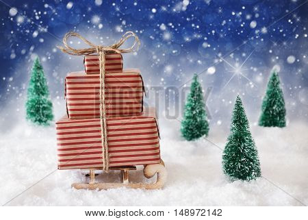 Sleigh With Christmas Gifts Or Presents. Snowy Scenery With Snow And Trees. Red Background With Snowflakes And Twinkling Stars