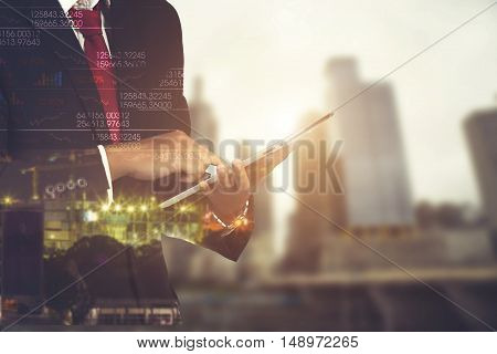 Double Exposure Of Businessman Using The Tablet With Cityscape And Financial Graph On Blurred Buildi