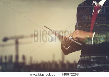 Double Exposure Of A Businessman And A City Using A Tablet Over Construction Background