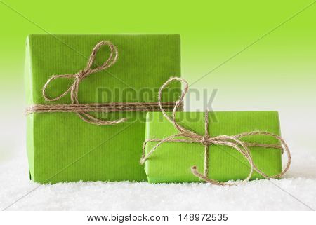 Two Green Christmas Gift Or Present On Snow. Card For Birthday Or Seasons Greetings. Natural looking Ribbon. Green Background