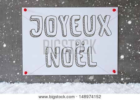 Label With French Text Joyeux Noel Means Merry Christmas. Urban And Modern Cement Wall As Background On Snow With Snowflakes.