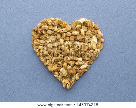 Heart shape muesli on a blue rugged paper background