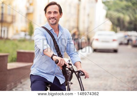 Activate your life. Cheerful delighted adult man smiling and riding a bike while resting outside