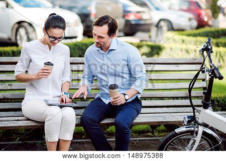 Enjoy the success. Young ambitious colleagues drinking tasty coffee in the park and looking for new ideas.