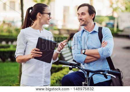 You will not believe. Happy ambitious woman telling her young male colleague on a bicycle surprising news.