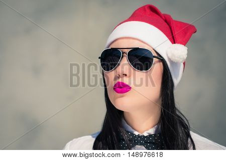 Portrait close up of a pretty young woman in Santa Claus hat and sunglasses with bright painted lips