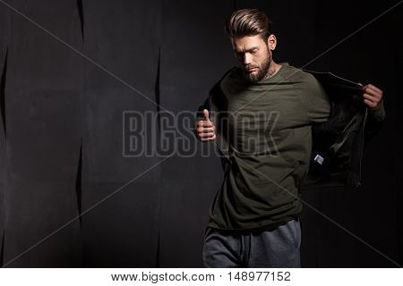 Man with beard in green t-shirt on gray cement background looking down