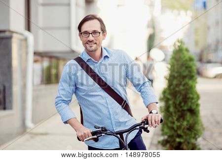 I like my walk. Handsome positive man smiling and riding on a bike while walking on the street.
