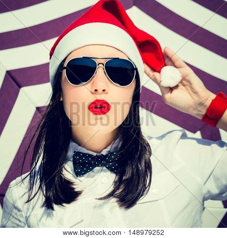 Portrait close up of a pretty young woman in Santa Claus hat and sunglasses with bright painted pink lips next to striped background