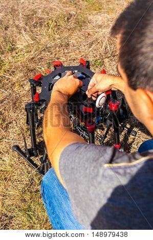 The process of setting up a copter before flight. The man makes all the necessary adjustments before the flight on the drone.