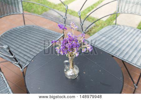 Purple Flower In Glass Vase, Wicker Chair On Patio