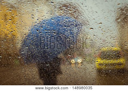 A blurry silhouette with umbrella on a city street seen through wet window with focus on some water drops. Toned effect