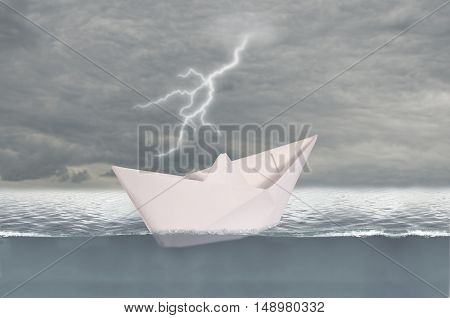 Paper ship on day stormy ocean background
