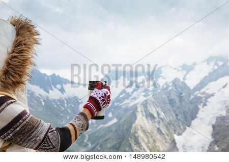 Travelers drinking tea in thermos mug in mountains with snow, winter hiking