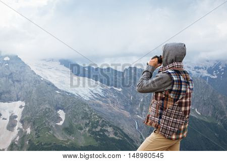 Man drinking hot coffee in thermos mug and looking into the mountains in snow, winter hike, cold season