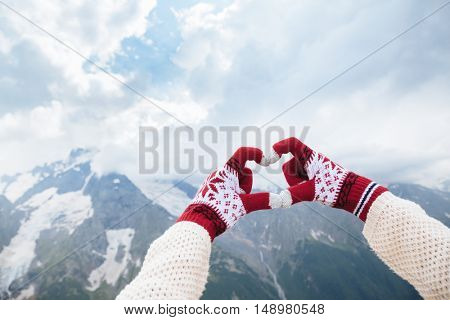 Closeup photo of hands in gloves showing love to the mountains, winter travelling
