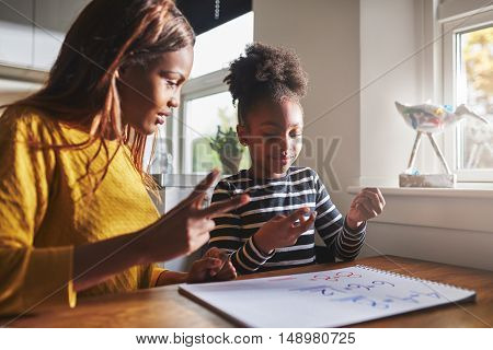 Patient mom teaching daughter schoolwork at home black family