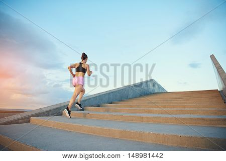 Low angle view of a fit healthy young woman jogging up a flight of outdoor concrete stairs at sunrise in an active lifestyle concept