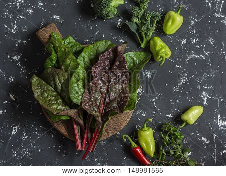 Fresh swiss chard pepper broccoli thyme oregano and spices on a dark background. Food background