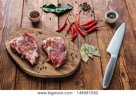 Meat with some condiment on kitchen table. Ready for cooking.