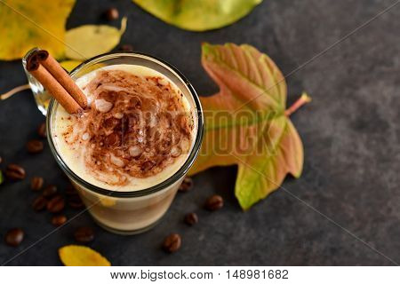 Warm spicy drink - latte with cinnamon and pumpkin on a black background