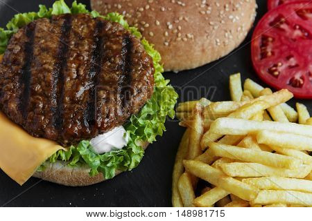 Beef hamburger grill french fries pickled cucumber tomato cheese